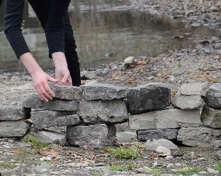 Image info: Build Up Break Down, video still, 2018. Credit: Fehn Foss. Hands building rock wall