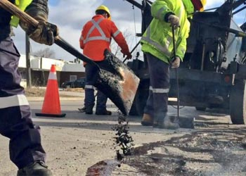 City road maintenance crew filling potholes with asphalt