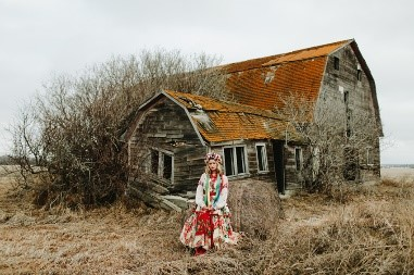 Photo info: Featured, Lianna Makuch. Photo credit: Mat Simpson. Dilapidated barn in background. woman in colourful dress in foreground.