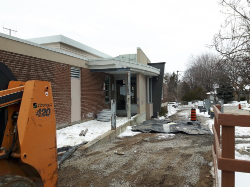 An image of the contruction scene at Broadlands Community Centre that includes a view of the side of the buliding, an entry way and a fork lift.