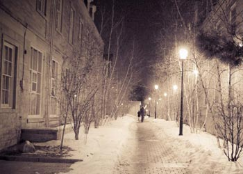 Person walking down snow covered path between two buildings at night