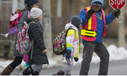 A crossing guard escorts a group of children across the road.