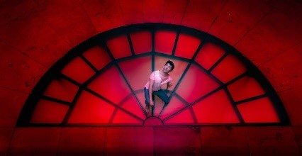 Performer on red stage. Black outline of a window - 1/2 circle. With bars.