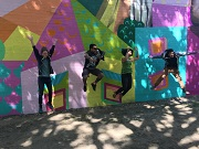 Artists jumping in front off a brightly painted street are wall.