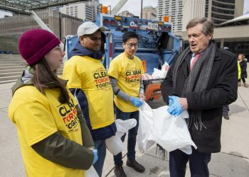 Mayor Tory meets three volunteers picking up garbage in Nathan Phillips Square.