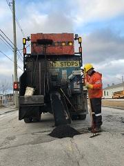 A City worker uses a machine to fill a pothole.