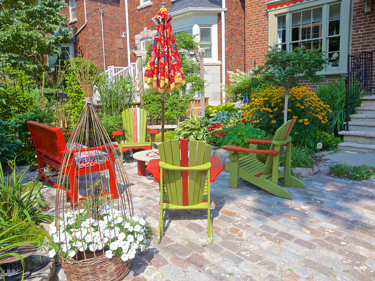 Colourful chairs and a table are surrounded by beautiful flowers