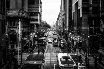 Black and white photograph of a busy city street filled with street cars, cars, and pedestrians.
