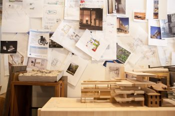 Studio with a wall filled with architectural drawings and photos. In front of this, small models of a building are placed on a table.
