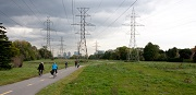 Cyclists on a path with greenlands and power lines.
