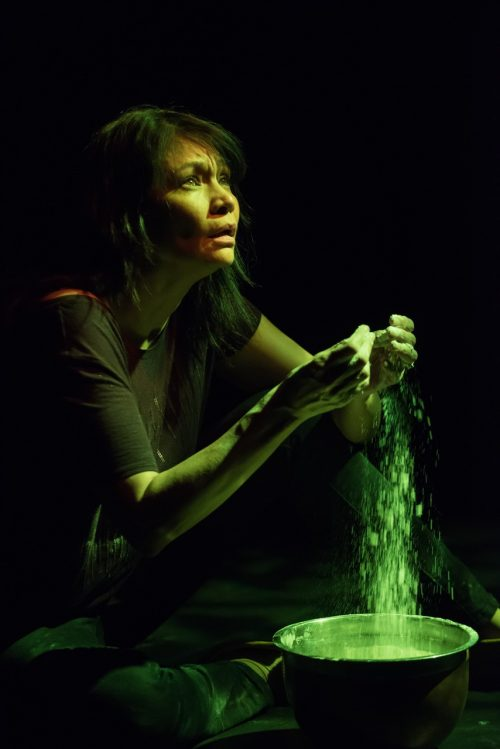 Photo info: Michelle Thrush in Inner Elder. Photo credit: Ben Laird. Woman with powder falling from hands into bowl