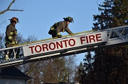 Two fire fighters on a ladder saying Toronto Fire.