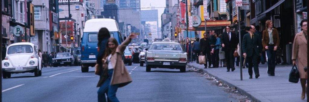 Two people crossing Yonge St in the 70s/80s with cars and lots of people in summer in the 70s