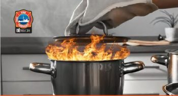 Hand wearing oven mitt putting a lid on a flaming pot