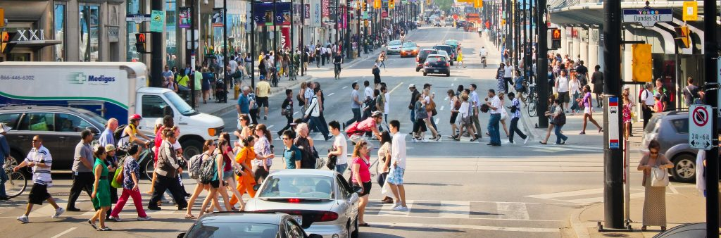 Image of Yonge Street by Dundas with pedestrians and cars crossing east / west. This is in summer