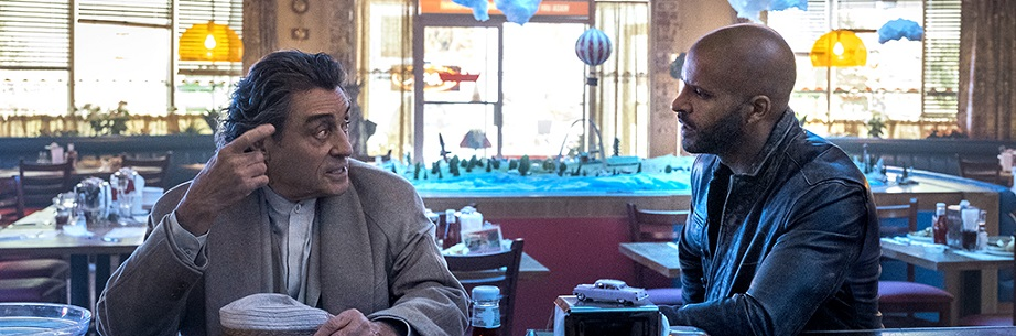 Actors Ian McShane and Ricky Whittle sit in diner.
