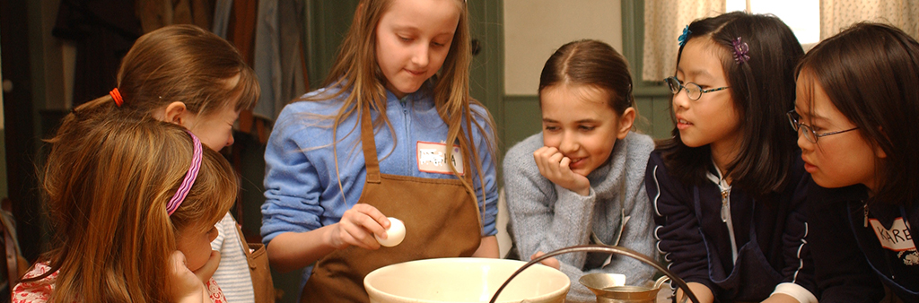 Photo of children standing around a table in aprons cracking eggs and making batter.