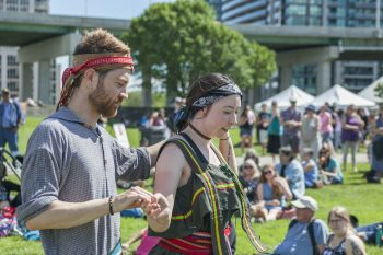 During the summer, a bearded man wearing a bandana holds hands with a woman in short sleeves and they dance.