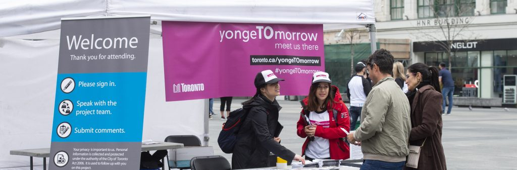 City Staff talking with people about the yongeTOmorrow study, at a booth promoting the project