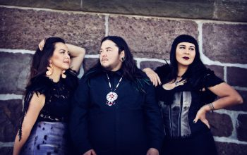 An Indigenous man wearing a beaded necklace stands in front of a brick wall and is flanked by two Indigenous women.