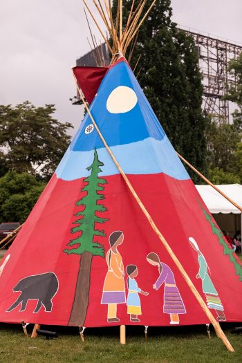 A traditional Indigenous tipi has colourful patterns and images including an evergreen tree, bear, the moon, and female figures.