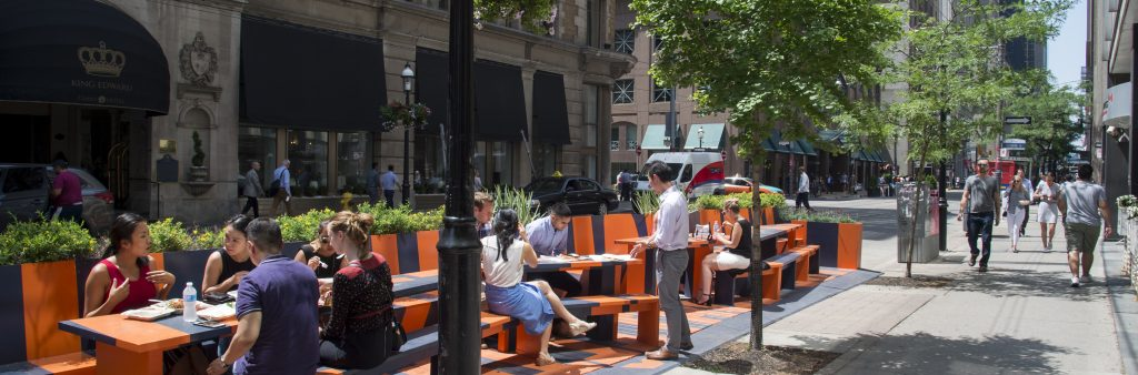 People sitting at parklet on road