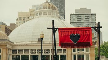 A banner from the Red Embers installation hanging in front of the Allan Gardens Conservatory. The flag is red and has a black heart on it. It is hung on charred-black gates.
