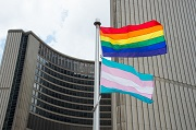 Rainbow and Transgender flags on flag pole with City Hall buildings in background.