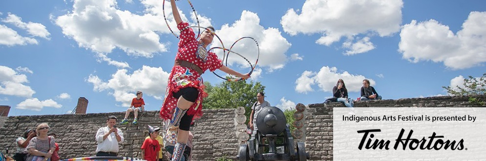 Hoop Dancer Rhonda Doxtator in a red polka-dot dress dances with a hoop against a blue sky.