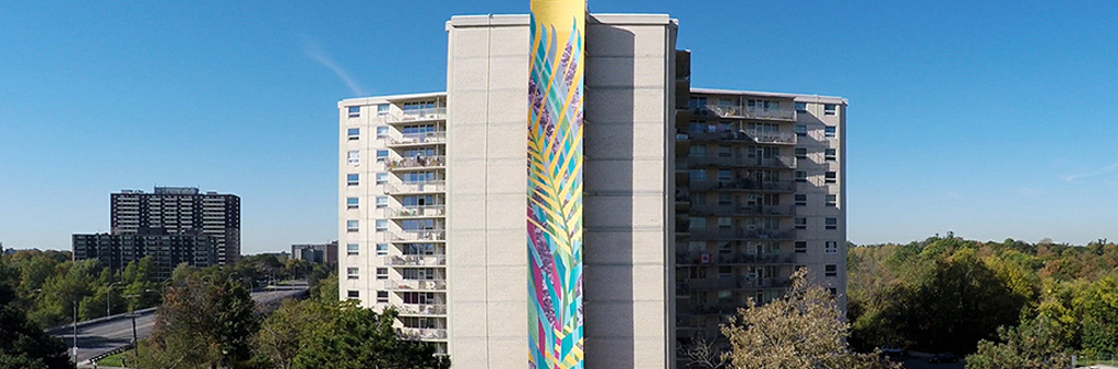 Colorful mural banner painted on side of a tall building