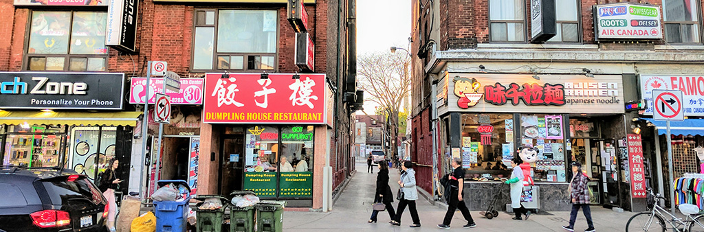 A group of attached historic buildings 3 storeys in height occupied by different retail tenants in Toronto's Chinatown, along Spadina Avenue is shown