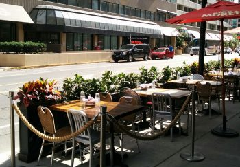 Image of a curbside café. In this configuration, the outdoor seating is located on a raised platform placed in the roadway. The platform is level with the curb so that the outdoor seating is accessible from the sidewalk.