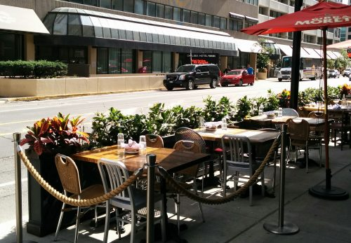 Image of a curbside café. In this configuration, the outdoor seating is located close to the curb. Pedestrians pass through between the frontage of the establishment and the outdoor seating area