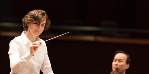Image info: Tania Miller. Conductor, with musician in background.