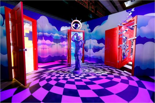 room with clouds painted on walls. 3 red doors, spiral, checkerboard floor. Statue and eye.