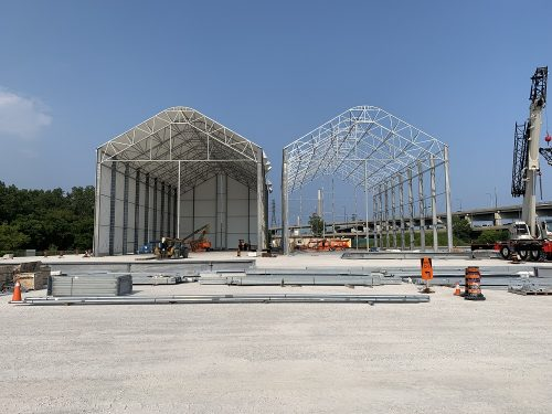 Image of Gardiner Expressway Strategic Rehabilitation, Jarvis to Cherry fabrication site located on lands near Lakeshore Blvd E and Cherry St. Image features two large tent structures in the process of assembly straight on view, one with a canvas cover and the other just a metal frame with the Gardiner Expressway in the background.