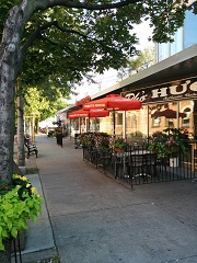 Image of a sidewalk café in Toronto. The outdoor seating area with red umbrellas is located against the front window of the business.