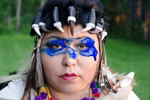 Image info: Jaene Castrillon - A Celebration of Darkness, Photo: courtesy of Jackie Lozer .Woman with blue paint around eyes, claws around forehead.
