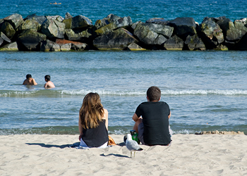 A couple sitting on the beach watch children playing in the lake.
