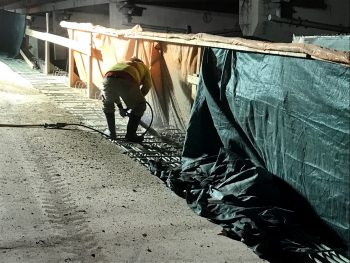Image of a construction worker chipping the concrete curb along the Gardiner Expressway York-Bay-Yonge off-ramp