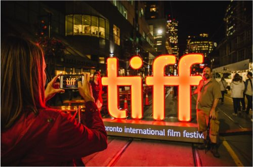 TIFF sign. Person taking photo of it. At night.