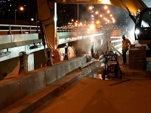 Image of westbound Gardiner Yonge-Bay-York off-ramp work zone, crews remove concrete parapet wall at the top of the ramp.