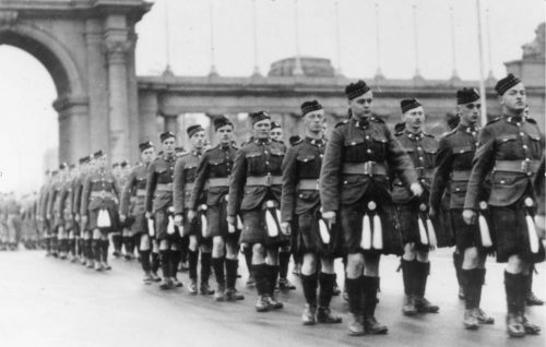 Black and White photo. Historic. Troops in uniforms (kilts) marching from Princes' Gate.