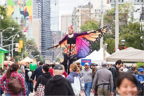 performer in butterfly costume, on stilts in crows