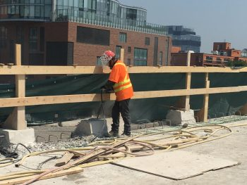 Image of construction worker chipping concrete on Gardiner Expressway York-Bay-Yonge off-ramp with safety netting and temporary wooden rails in the background