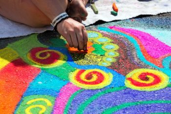 Close-up of person's hand drawing a colourful mural on pavement.