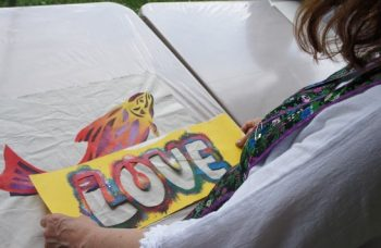 Over shoulder view of a woman holding and looking down at a LOVE stencil placard on a white table with a colourful drawing of a fish in the background.