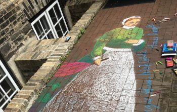 A colourful mural drawing of a woman on the pavement.