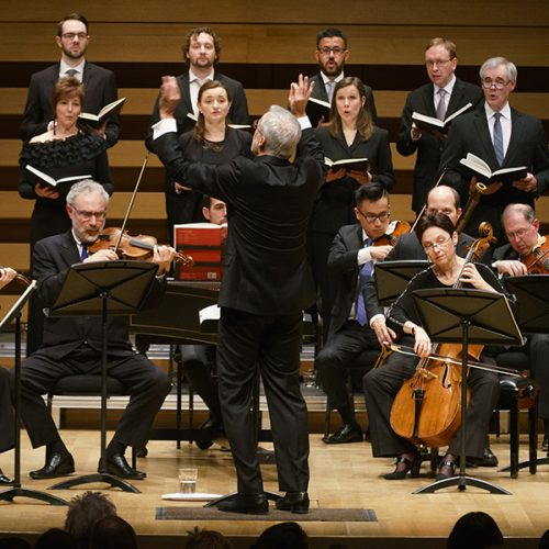 Conductor leading musicians and singers.