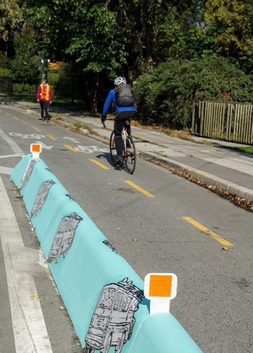 Photo showing concrete jersey barrier next to cyclist riding in bike lane